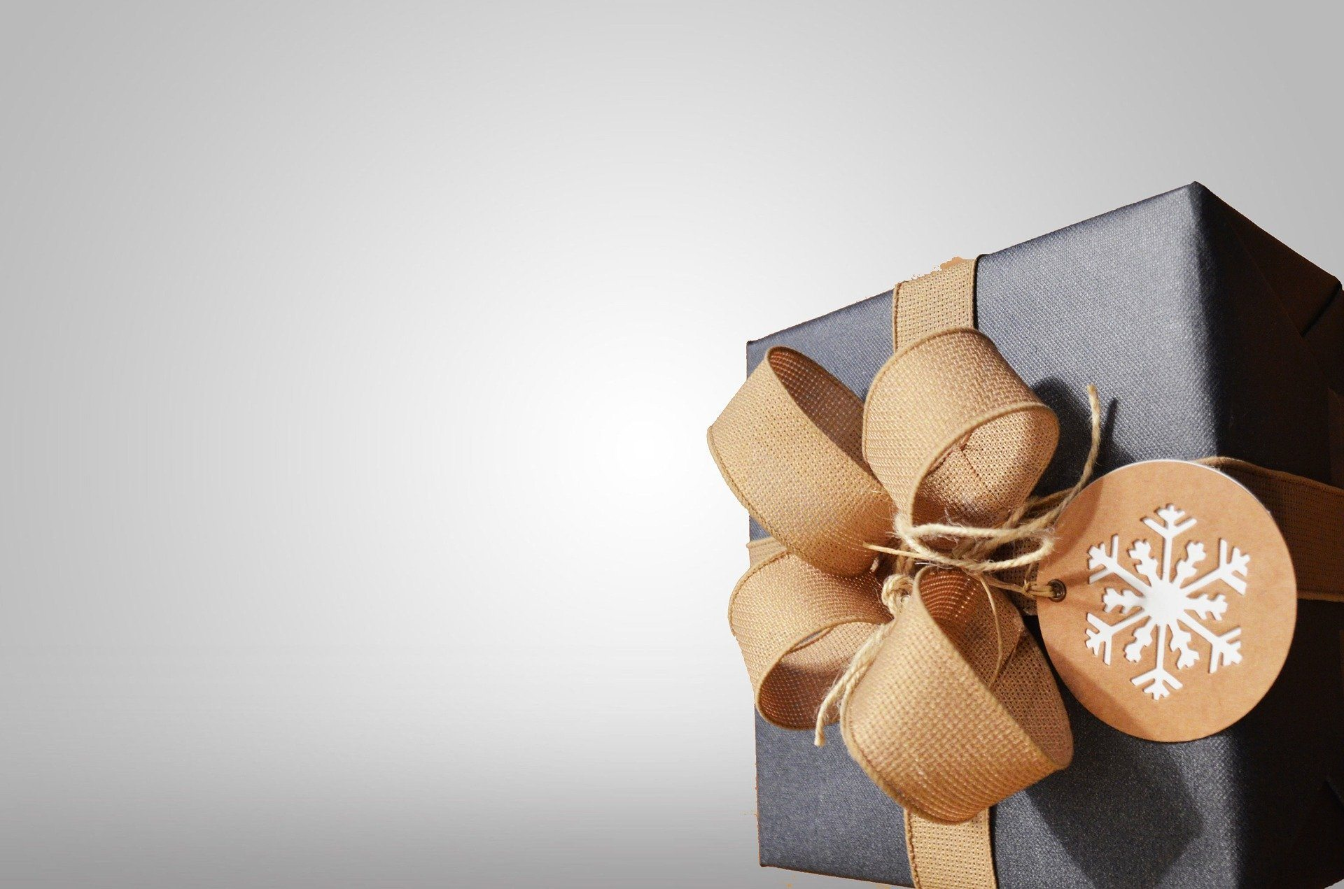 Christmas present wrapped in a brown box with a gold ribbon that could be a skincare product